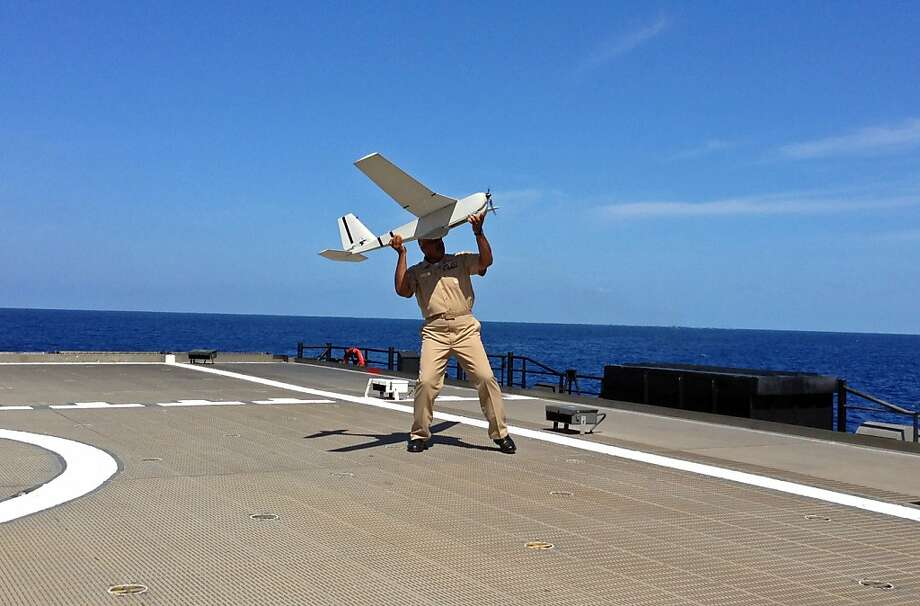 U.S. Navy Rear Admiral Sinclair Harris prepares lo launch a UAS (unmanned aircraft system) named Puma from the deck of his high speed vessel Swift near Key West, Florida, Friday, April 26, 2013. The U.S. Navy on Friday began testing two new aerial tools, borrowed from the battlefields of Afghanistan and Iraq, that officials say will make it easier to detect, track and videotape drug smugglers in action.  Photo: Ben Fox, Associated Press