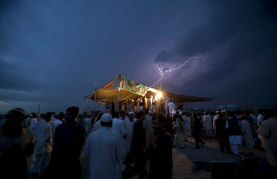 Lightning flashes as political supporters of the Pakistan Muslim League hold a meeting under tight security due to ongoing attacks on political rallies and parties' election offices, in Islamabad, Pakistan on Friday, April 26, 2013. The Muttahida Qaumi Movement has ordered the closure of election offices in Karachi following a blast that killed many party workers.  Photo: B.K. Bangash, Associated Press