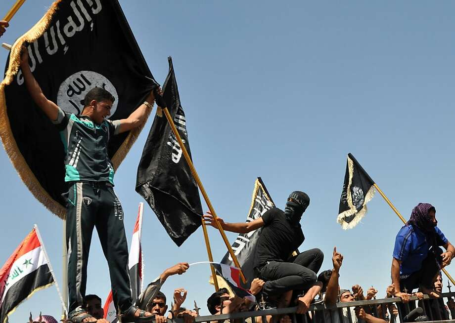 Masked Sunni protesters wave Islamist flags during an antigovernment rally in Fallujah. The Shiite-led government has been the target of rising Sunni anger over perceived mistreatment. Photo: Bilal Fawzi, Associated Press