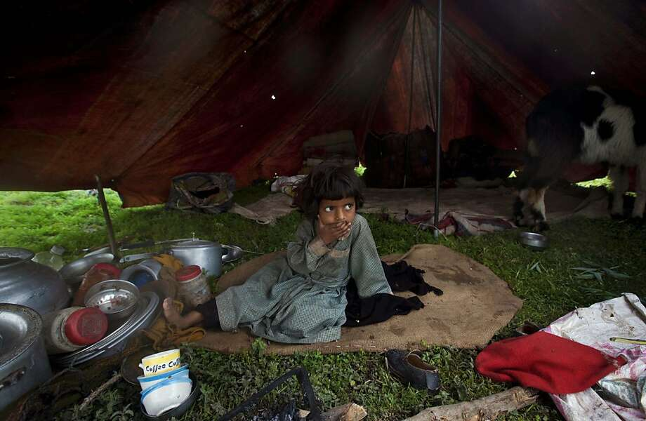A young Kashmiri Bakarwal nomad girl sits inside her temporary camp on the outskirts of Srinagar, India, Friday, April 26, 2013. Bakarwals are nomadic shepherds of India's Jammu Kashmir state who wander in search of good pastures for their cattle.  Photo: Dar Yasin, Associated Press