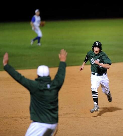 Shenendehowa's Kyle McAlonie, right, runs for third as coach Greg Christodulu signals to apply the b