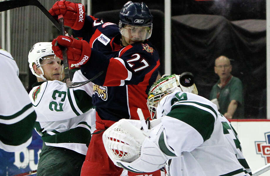 Defenseman Steven Kampfer, left, applies the pressure the Aeros hope to maintain against the Griffins as Aeros goalie Darcy Kuemper stops a shot by Grffins left winger Tomas Tatar, one of his 36 saves on the night. Photo: Cody Duty, Staff / © 2013 Houston Chronicle