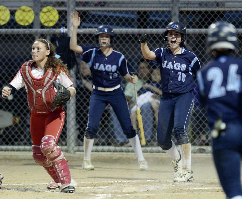 Johnson's Kate Weinman (right) and Kylie Rittiman cheer their teammates after Weinman scored during the Jaguars' two-run second inning. Judson catcher Nicole Shedd awaits a throw. Photo: Darren Abate / For The Express-News