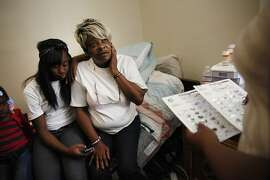 Zina Byes (right), caregiver to Harrison Hotel resident Nancy Johnson (center), discusses Johnson's medication with her as Johnson sits with her granddaughter Jasmine Wilson (left) , 13, in Johnson's room on Friday, April 12, 2013 in Oakland, Calif.