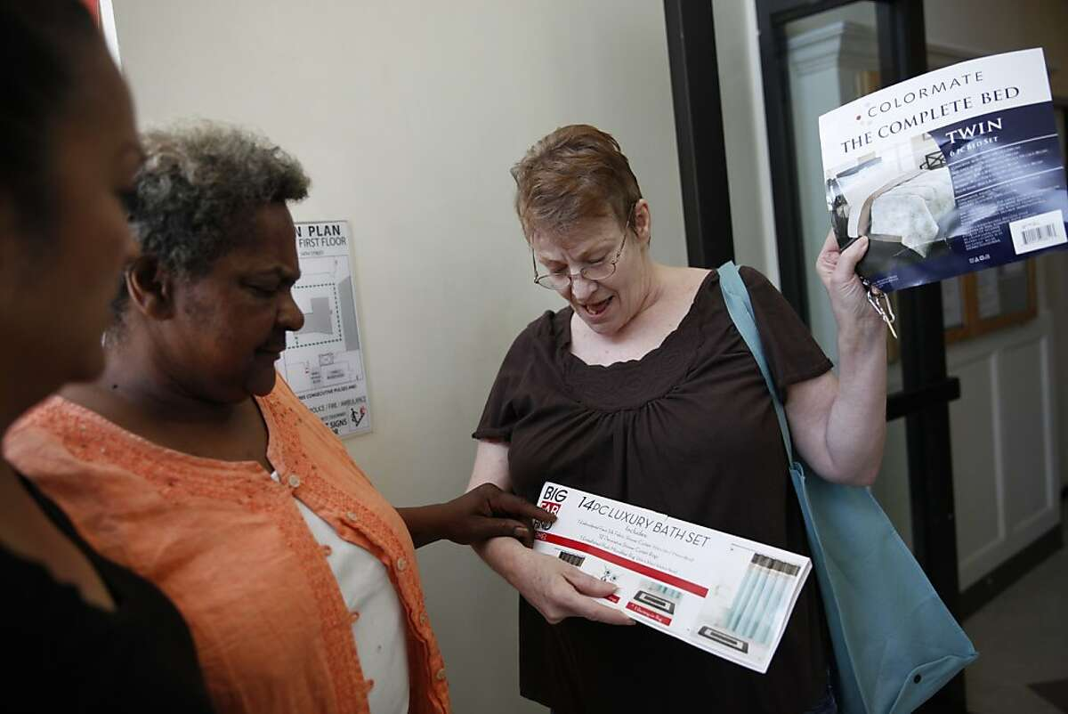 Harrison Hotel resident Linda Lineberry (right) , 65, shows fellow resident Valerie Simmons (center), and Lifelong clinical case manager Cecilia Esguerra (left) items she is considering to furnish her new room at the Harrison Hotel on Friday, April 12, 2013 in Oakland, Calif.
