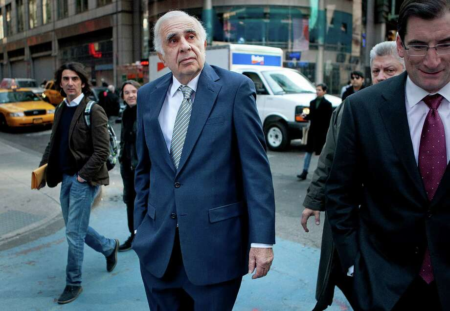 Carl Icahn, billionaire investor and chairman of Icahn Enterprises Holdings LP, center, walks outside of the Nasdaq MarketSite with Robert Greifeld, chief executive officer and president of Nasdaq OMX Group Inc., in New York, U.S., on Tuesday, March 27, 2012. Icahn bought a controlling interest in Sugar Land-based CVR Energy Inc. in 2012. The company is now considering a potential sale or other strategic options and recently sold a terminal in Cushing, Oklahoma to Plains All American. Robert Greifeld Photo: Scott Eells, 1009729