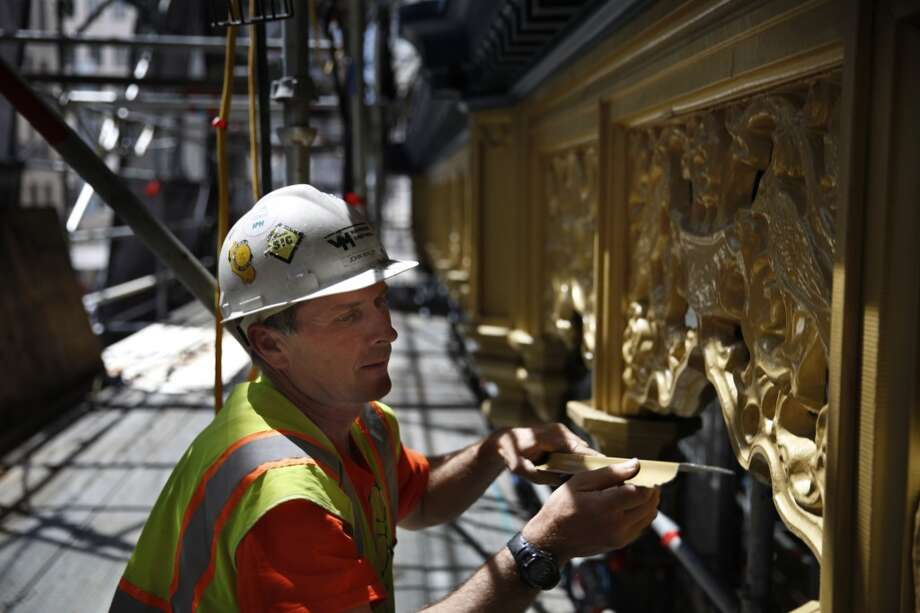 John Walsh of Van-Mulder Sheet Metal, replaces part of the framing on the Hallidie Building on Monday, April 22, 2013 in San Francisco, Calif. The building underwent rehabilitation to repair the decorative sheet metal frieze panels and cornices, balconies, and fire escapes and repainted in its original blue and gold. It is believed to be the first American building to feature a glass curtain wall.