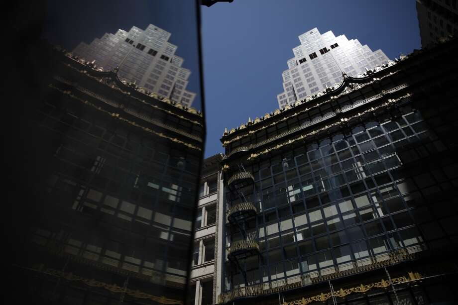 The front of the rehabilitated Hallidie Building (right) is seen reflected in a plastic panel on Friday, April 26, 2013 in San Francisco, Calif. The building underwent rehabilitation to repair the decorative sheet metal frieze panels and cornices, balconies, and fire escapes and repainted in its original blue and gold. It is believed to be the first American building to feature a glass curtain wall.