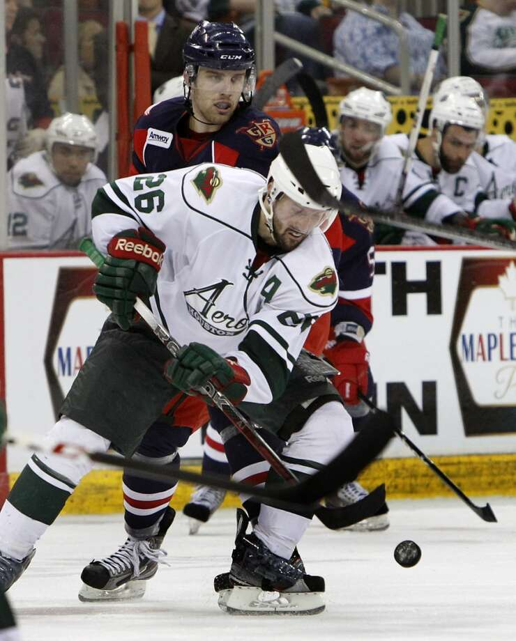 Aeros center David McIntyre, front, takes control after a faceoff with Grand Rapids Griffins center Riley Sheehan, back, during the second period of their first playoff game against the Grand Rapids Griffins at the Toyota Center Friday, April 26, 2013, in Houston. The Aeros won 3-0. (Cody Duty / Houston Chronicle)
