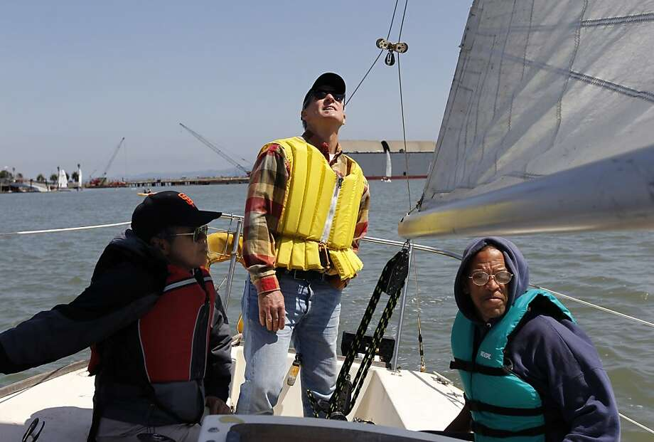 Matt Sander (center) skippers the Ole Yeller sailboat for Danny Wong (left), Milton Winstead and other visitors to the Treasure Island Sailing Center. Photo: Paul Chinn, The Chronicle