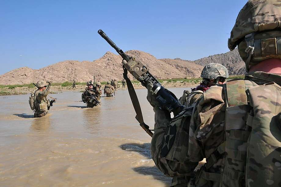 In this April 10, 2013 photo released by the U.S. Army, U.S. Soldiers with Charlie Company, 1st Battalion, 38th Infantry Regiment, 4th Brigade Combat Team, 2nd Infantry Division cross the Tarnak river in the Panjwai district of Kandahar province, Afghanistan on a two-day mission to clear the area of explosives caches. The Taliban have announced they will launch their spring offensive on Sunday, April 28, 2013, signaling plans to step up attacks as the weather warms across Afghanistan, making both travel and fighting easier.  (AP Photo/Sgt. Kimberly Hackbarth, U.S. Army) Photo: Sgy. Kimberly Hackbarth, Associated Press