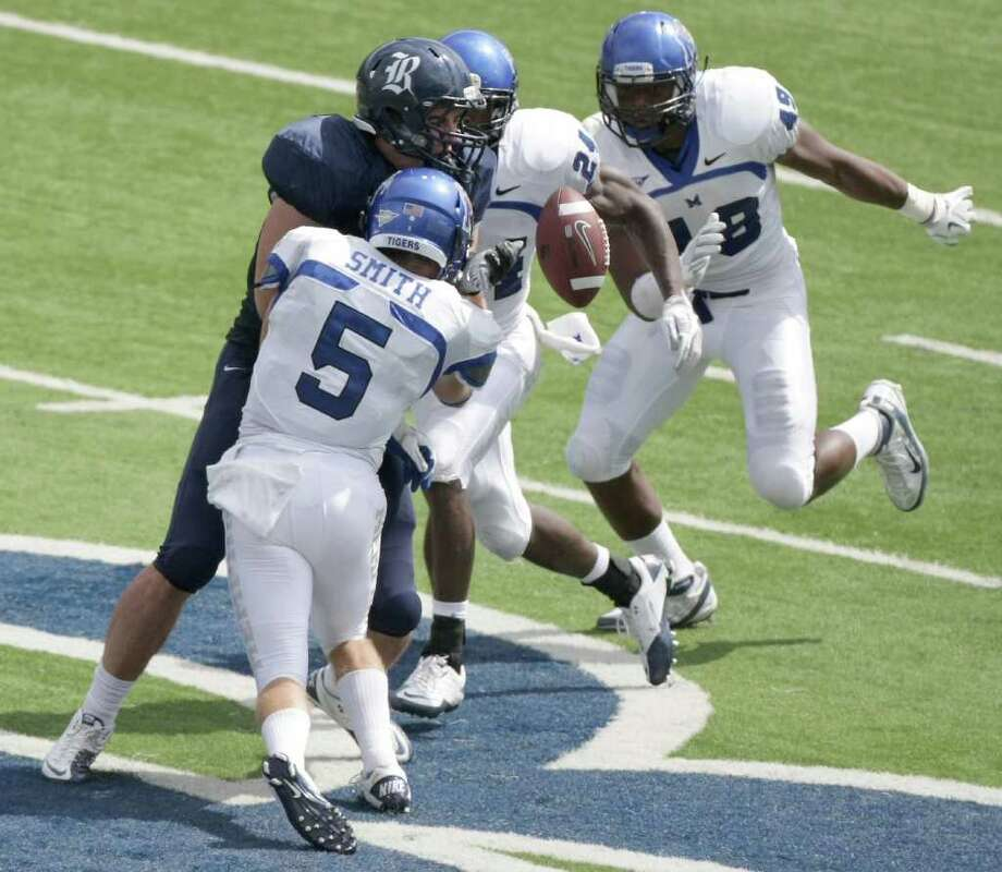 Rice University tight end Luke Willson (82) has the ball knocked out of his hands by Memphis University defensive back Cannon Smith (5) and other Tiger secondary players in the third quarter of a game at Rice Stadium in Houston on Oct. 8, 2011. Rice University won 28-6. Photo: Nick De La Torre, Houston Chronicle / © 2011  Houston Chronicle
