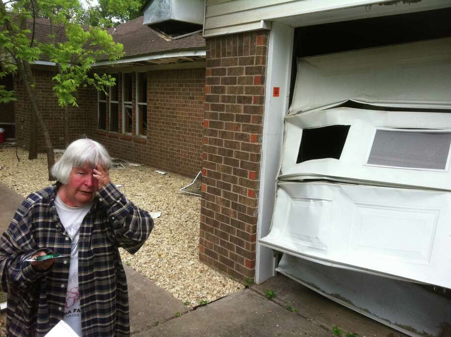 "Jean Smith, who lives in the devastated ""Zone 3"" of West, 250 yards from the epicenter of the town's deadly fertilizer plant explosion, walks by her crumpled garage door Saturday while surveying the damage to her home for the first time. April 27, 2013. Photo: Craig Kapitan / San Antonio Express-News"