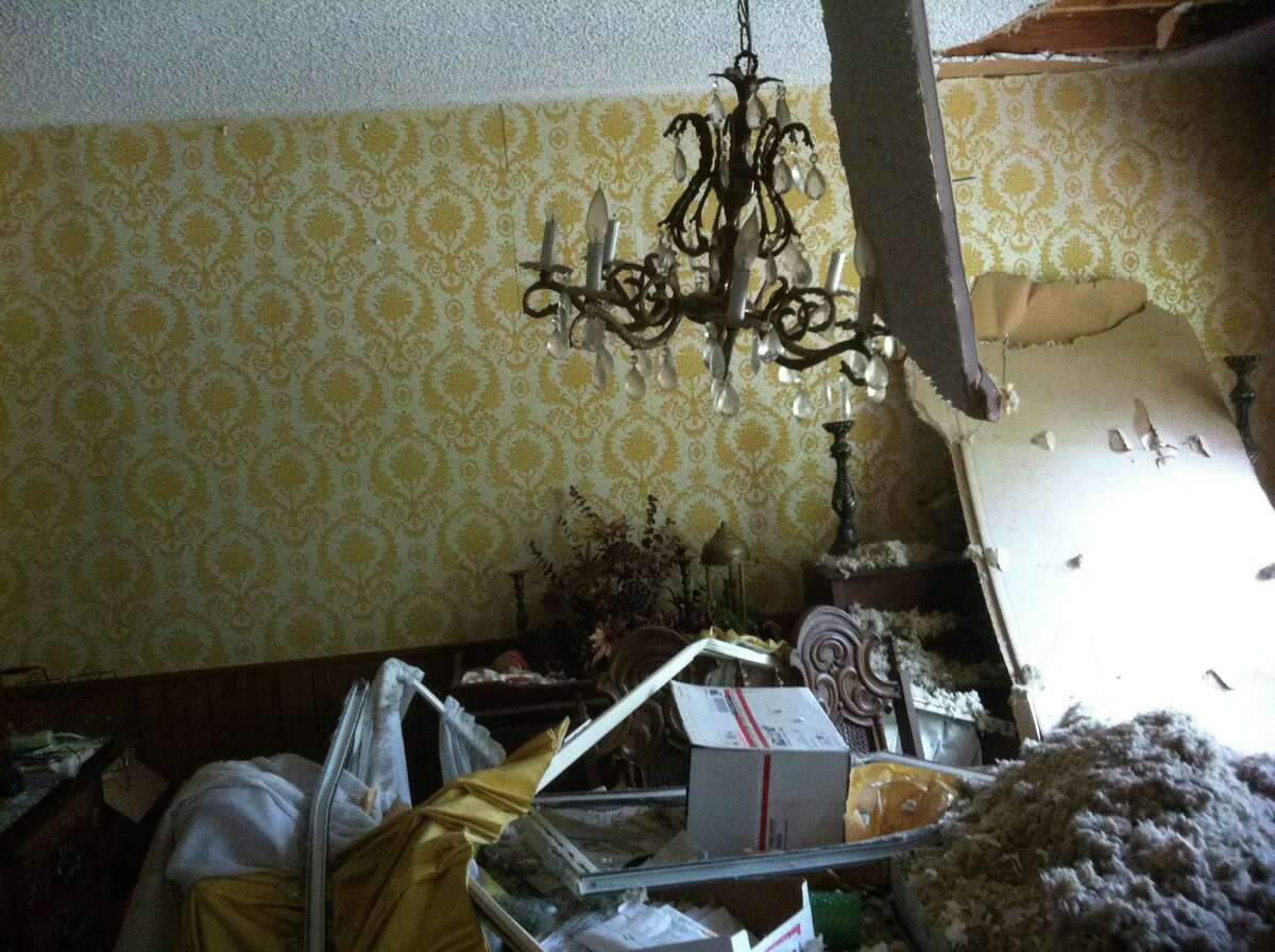 George and Jean Smith's dining room chandelier hangs askew underneath their home's destroyed ceiling. They were allowed to survey their home, inside West's devastated