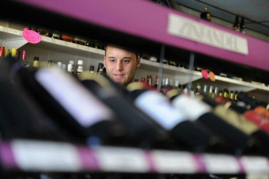 Owner Brian Mendes inspects the shelves at Sandy Hook Wine and Liquor in Sandy Hook, Conn. on Wednesday, April 24, 2013.  The business recently changed ownership, with the new owner coming from Bristol.  The Sandy Hook Spring Fling block party will be held in downtown Sandy Hook on Saturday, April 27, 2013 from 11 a.m. to 4 p.m. in an effort to welcome the community back to the local businesses.  The event will feature live music and promotions and is presented by the Sandy Hook Organization for Prosperity. Photo: Tyler Sizemore / The News-Times