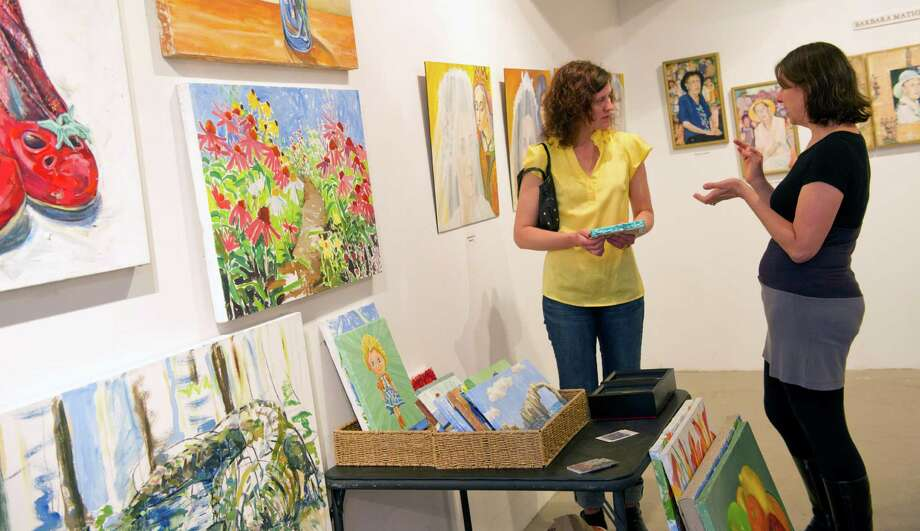 Celeste Frye, left, buys a painting from Alissa Siegal, right, at the Loft Artists Association's final open studios in Stamford, Conn., on Saturday, April 27, 2013. Photo: Lindsay Perry / Stamford Advocate