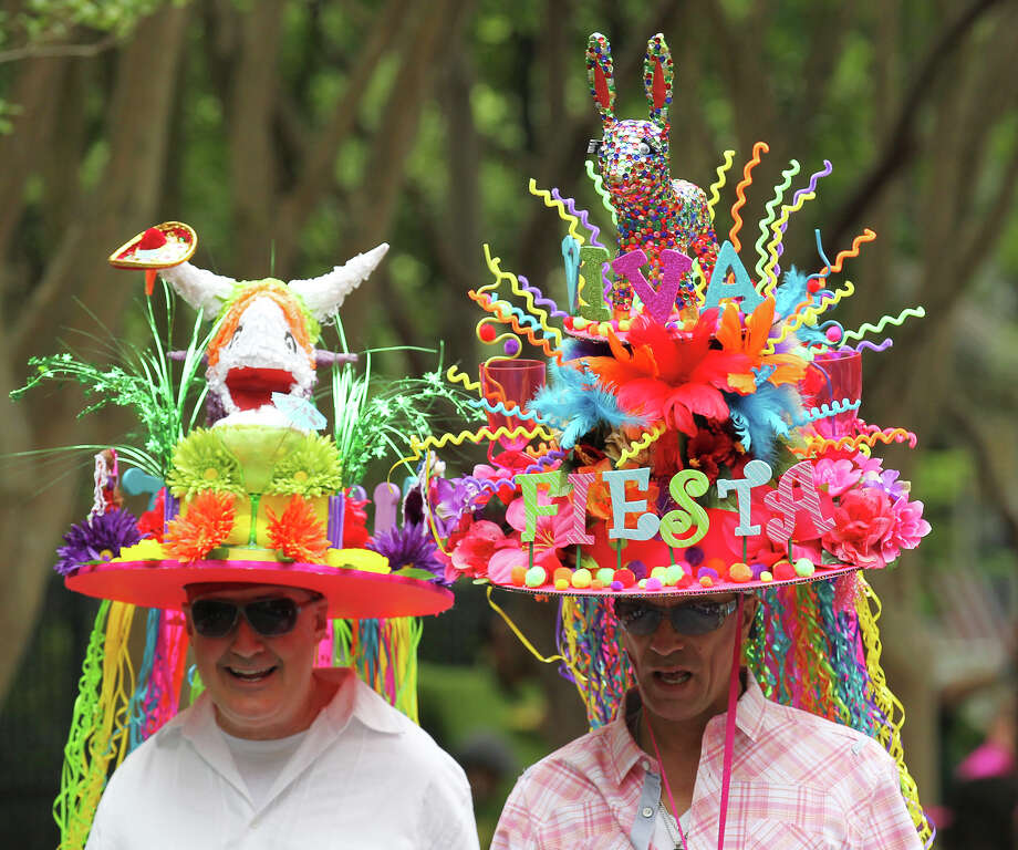 Tye Wichert (center) and Guy Pritchard wear festive hats made by Wichert at the King William Fair Parade on Saturday, Apr. 27, 2013. Wichert said he spent about a week making the hats and has created a different one for the past five years. Photo: Kin Man Hui, Express-News / © 2013 San Antonio Express-News