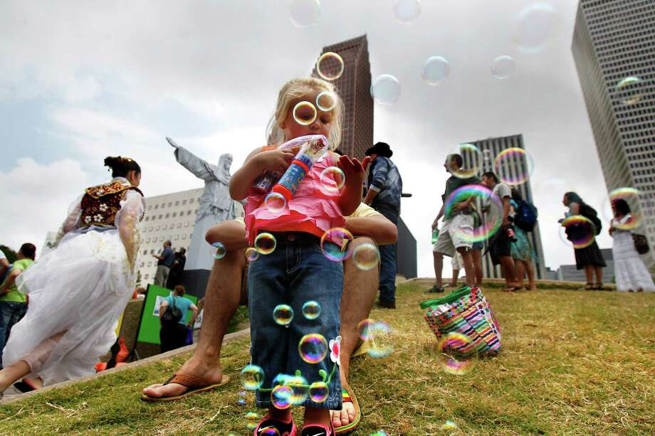 "Haley Theliard, 2, blows bubbles at the 2013 Houston International Festival, Saturday, April 27, 2013, in Houston. ""It's real diverse, a whole bunch of different cultures come together,"" her dad, Darren said.  Photo: Cody Duty, Houston Chronicle / © 2013 Houston Chronicle"