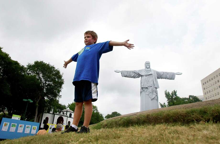 Dutch Binetti, 7, stands in front of the statue of Christ the Redeemer, a replica of the statue in Rio de Janeiro, Brazil, at the 2013 Houston International Festival, Saturday, April 27, 2013, in Houston.  Photo: Cody Duty, Houston Chronicle / © 2013 Houston Chronicle