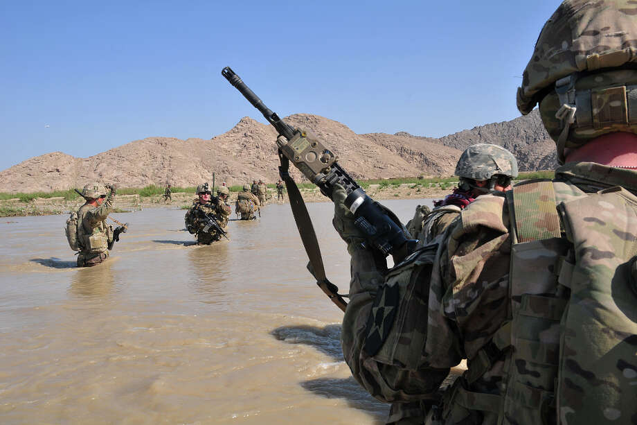 In this April 10, 2013 photo released by the U.S. Army, U.S. Soldiers with Charlie Company, 1st Battalion, 38th Infantry Regiment, 4th Brigade Combat Team, 2nd Infantry Division cross the Tarnak river in the Panjwai district of Kandahar province, Afghanistan on a two-day mission to clear the area of explosives caches. The Taliban have announced they will launch their spring offensive on Sunday, April 28, 2013, signaling plans to step up attacks as the weather warms across Afghanistan, making both travel and fighting easier.  (AP Photo/Sgt. Kimberly Hackbarth, U.S. Army) Photo: Sgy. Kimberly Hackbarth