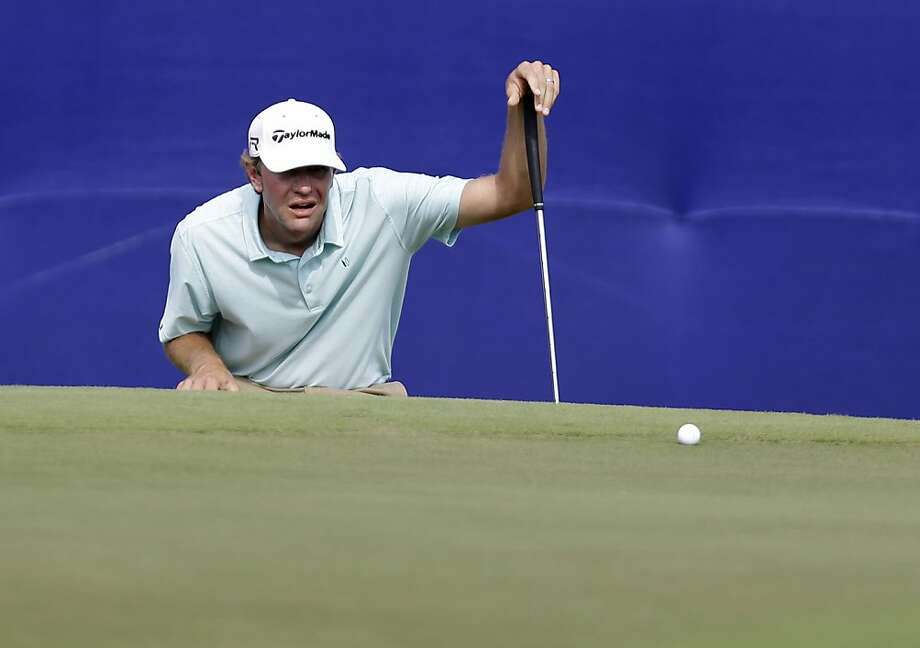 Lucas Glover sizes up a putt on the 18th green, where he made birdie for a round of 70. Photo: Gerald Herbert, Associated Press