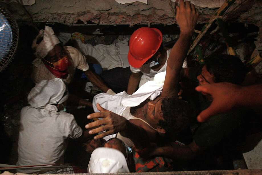 Rescuers carry a survivor three days after the eight-story building in Savar, Bangladesh, collapsed. Rescuers on Saturday reached the ground floor. Photo: Mohammad Asad / Getty Images