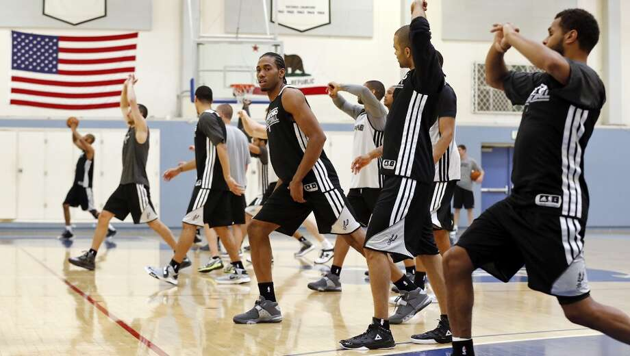 San Antonio Spurs' Kawhi Leonard (center) and teammates stretch during practice Saturday April 27, 2013 at Santa Monica College in Santa Monica, CA.
