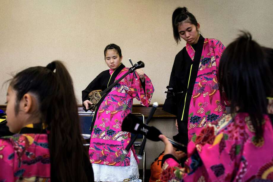 Kirari Henzan, center left, tunes up her instrument with the rest of her troupe before a performance at the 38th annual Cherry Blossom and Japanese Cultural Festival Saturday, April 27, 2013, at The Armory in Seattle. The festival boasted over 60 traditional performing arts and craft stations, drawing acts from as far away as Okinawa, Japan. Photo: JORDAN STEAD, SEATTLEPI.COM / SEATTLEPI.COM