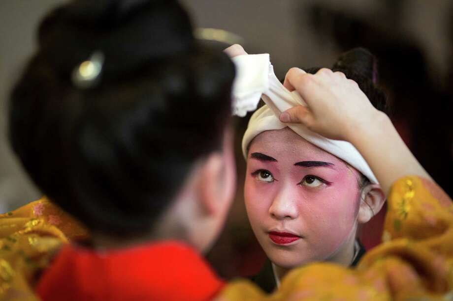 Moments before taking the stage, performers secure a headdress at the 38th annual Cherry Blossom and Japanese Cultural Festival Saturday, April 27, 2013, at The Armory in Seattle. The festival boasted over 60 traditional performing arts and craft stations, drawing acts from as far away as Okinawa, Japan. Photo: JORDAN STEAD, SEATTLEPI.COM / SEATTLEPI.COM
