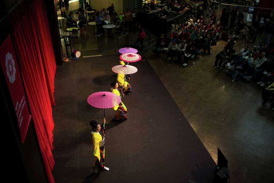 Dancers spin colorful umbrellas from the height of the stage at the 38th annual Cherry Blossom and Japanese Cultural Festival Saturday, April 27, 2013, at The Armory in Seattle. The festival boasted over 60 traditional performing arts and craft stations, drawing acts from as far away as Okinawa, Japan. Photo: JORDAN STEAD, SEATTLEPI.COM / SEATTLEPI.COM