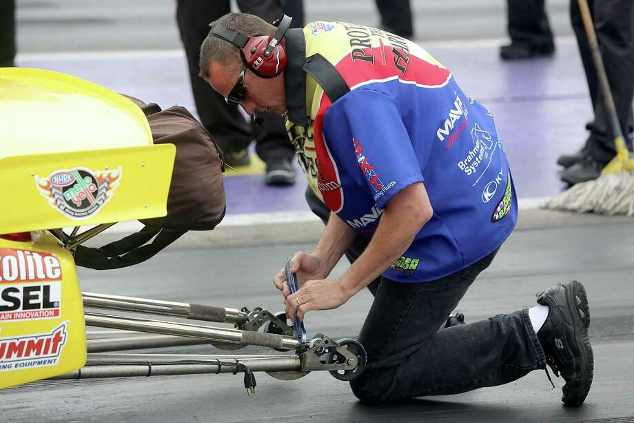 4/27/13: A Steve Kent mechanic works on the wheely bar before Kent's first qualification run on the second day of qualifying at Royal Purple Speedway in Baytown, Texas. Photo: Thomas B. Shea, For The Chronicle / © 2013 Thomas B. Shea