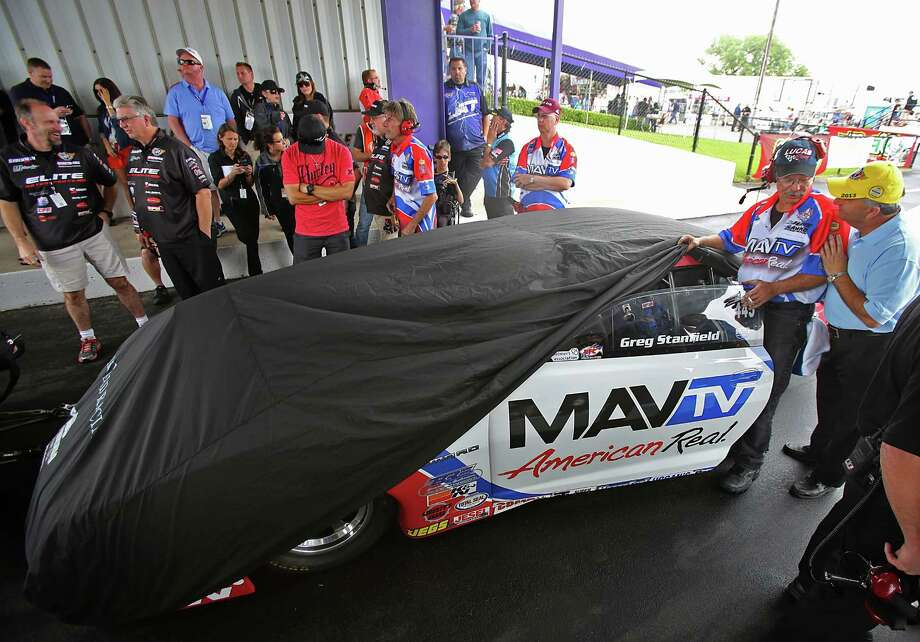 4/27/13: Pro stock Greg Stanfield car puts a tarp on his car during the rain delay on the second day of qualifying at Royal Purple Speedway in Baytown, Texas. Photo: Thomas B. Shea, For The Chronicle / © 2013 Thomas B. Shea