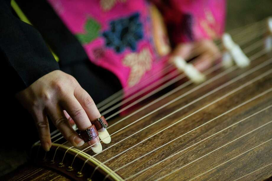 A musician tunes up her ryukyu koto at the 38th annual Cherry Blossom and Japanese Cultural Festival Saturday, April 27, 2013, at The Armory in Seattle. The festival boasted over 60 traditional performing arts and craft stations, drawing acts from as far away as Okinawa, Japan. Photo: JORDAN STEAD, SEATTLEPI.COM / SEATTLEPI.COM