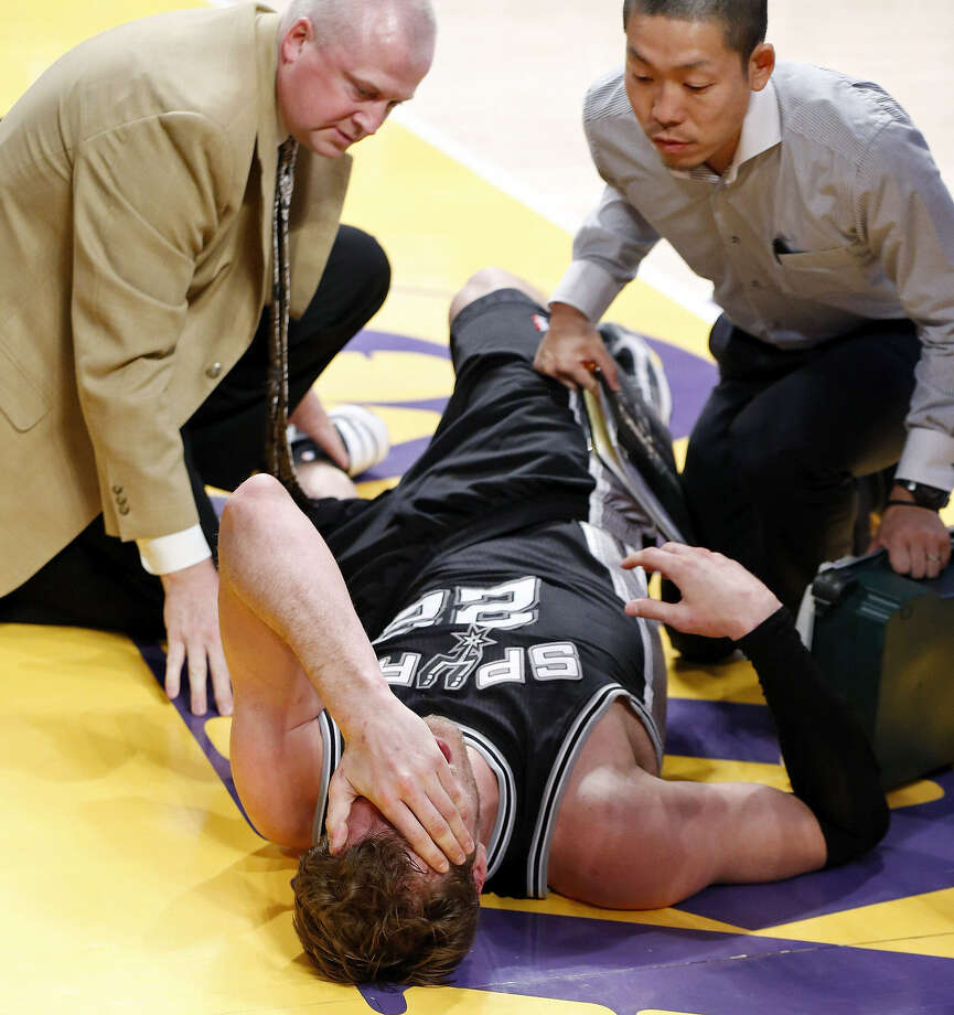 Spurs big man Tiago Splitter is tended to on the floor after spraining his left ankle during Friday's night's Game 3 victory in Los Angeles. He should be back for the next round. Photo: Edward A. Ornelas / San Antonio Express-News
