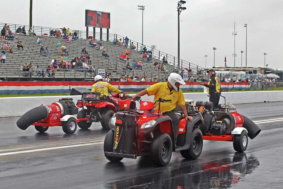 Powerful thunderstorms in the Houston  area forced the cancellation of Saturday's qualifying in the O'Reilly Auto Parts NHRA Spring Nationals at Royal Purdple Raceway in Baytown, but not before workers did their best to dry the track. Photo: Thomas B. Shea / © 2013 Thomas B. Shea