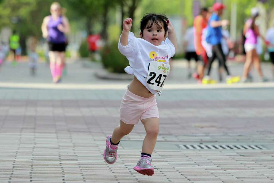 Harley Ngo, 2, jumps at the finish line in the Lemonade Day Kids 1K Fun Run at City Center on Saturday, April 27, 2013, in Houston. Photo: Mayra Beltran / © 2013 Houston Chronicle