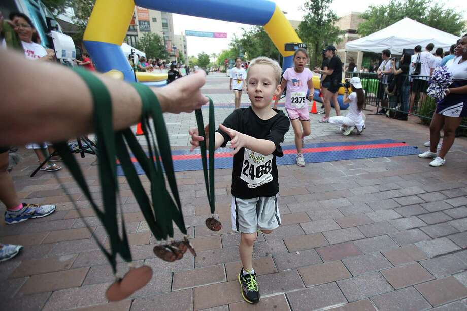 Nathan Patterson reaches for his medal after crossing the finish line of the Lemonade Day Kids 1K Fun Run at City Center on Saturday, April 27, 2013, in Houston. Photo: Mayra Beltran / © 2013 Houston Chronicle