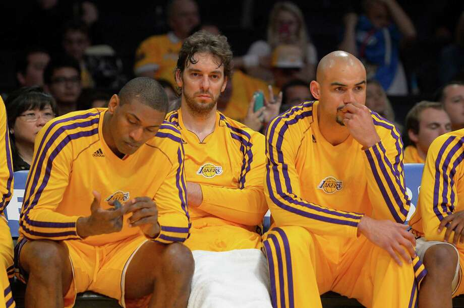 Metta World Peace, left, joins Pau Gasol and Robert Sacre on a Lakers bench made more glum by the news World Peace will miss Game 4 with an injury. Photo: Mark J. Terrill, STF / AP