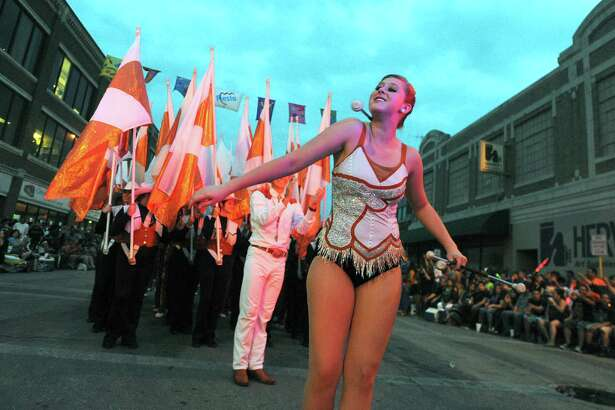 "The University of Texas Longhorn Band twirler makes her way down Broadway during the annual Fiesta Flambeau Night Parade on Saturday, April 27, 2013. The them of this year's parade was ""Celebrating San Antonio."""