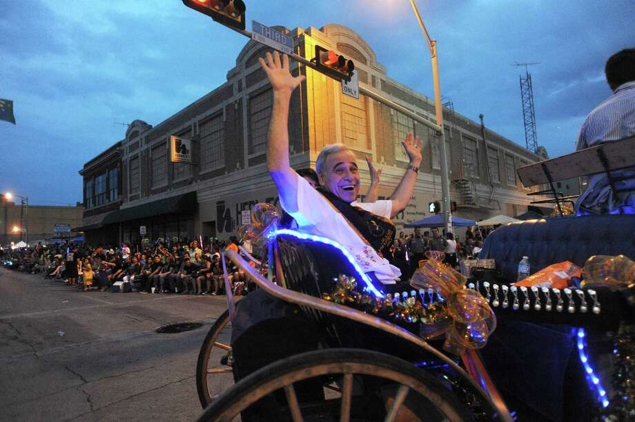 "Grand Marshal retired U.S. Representative Charlie Gonzalez waves from the intersection of Broadway and Third Street during the annual Fiesta Flambeau Night Parade on Saturday, April 27, 2013. The them of this year's parade was ""Celebrating San Antonio."" Photo: Billy Calzada, San Antonio Express-News / © 2013 San Antonio Express-News"