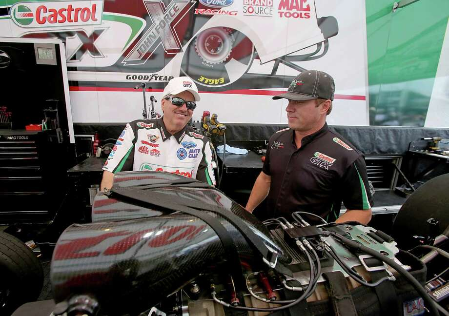 Funny Car driver John Force, left, and crew chief Mike Neff had plenty of time to talk during Saturday's rain delay at Royal Purple Raceway. They might not have that luxury during a finals featuring shortened turnaround times. Photo: Thomas B. Shea / © 2013 Thomas B. Shea