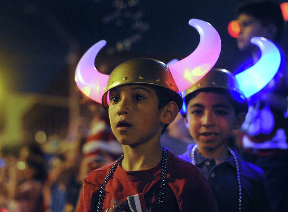 "Trae Chapa, left, and his friend, Eden Rodriguez watch the Fiesta Flambeau Night Parade on Saturday, April 27, 2013. The theme of this year's parade was ""Celebrating San Antonio."" Photo: Billy Calzada, San Antonio Express-News / © 2013 San Antonio Express-News"
