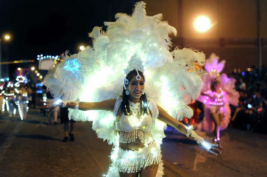 "Jessica Patino of Samba Vida dances her way down Broadway during the annual Fiesta Flambeau Night Parade on Saturday, April 27, 2013. The theme of this year's parade was ""Celebrating San Antonio."" Photo: Billy Calzada, San Antonio Express-News / © 2013 San Antonio Express-News"