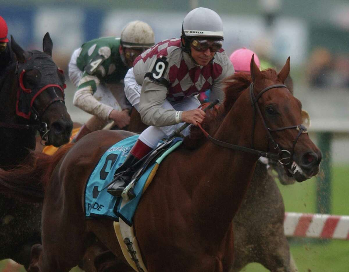 Funny Cide was named after his sire, Distorted Humor, and dam, Belle's Good Cide. Here, jockey Jose Santos on Funny Cide passes the clubhouse for the first time in the 128th running of the Preakness Stakes at Pimlico Race Course in Baltimore, Md., May 17, 2003. Funny Cide won the race.