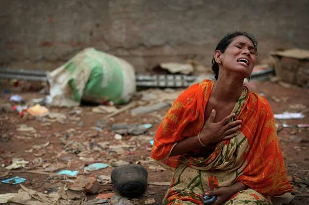 A woman cries out for her missing husband at the site of the garment factory building that collapsed Wednesday in Savar, near Dhaka, Bangladesh, Saturday, April 27, 2013. Police in Bangladesh took five people into custody in connection with the collapse of a shoddily-constructed building this week, as rescue workers pulled 19 survivors out of the rubble on Saturday and vowed to continue as long as necessary to find others despite fading hopes.(AP Photo/Wong Maye-E) Photo: Wong Maye-E, Associated Press / AP