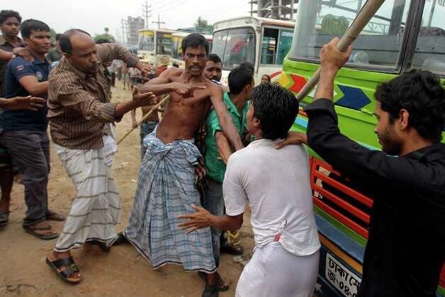 Bangladeshi garment workers beat a driver, second right, for not stopping a bus he was driving, during a protest against the collapse of an eight-storey building that housed several garment factories and poor working conditions of the employees, in Dhaka, Bangladesh, Saturday, April 27, 2013. (AP Photo/A.M. Ahad) Photo: A.M. Ahad, Associated Press / AP