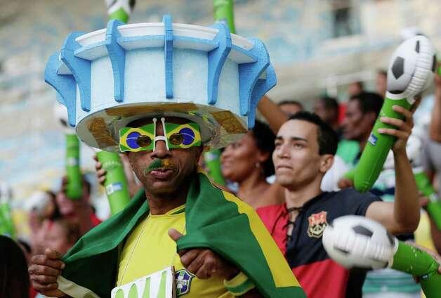 "A man wears a hat in the shape of the Maracana stadium as he arrives for the inauguration of the renovated Maracana stadium in Rio de Janeiro, Brazil, Saturday, April 27, 2013. The ""Temple of Football,"" as it's often called, is reopening as one of the most modern sporting venues in Brazil, but the improvements came amid widespread criticism related to allegations of overspending, protests against the stadium's privatization plans and construction delays. (AP Photo/Silvia Izquierdo) Photo: Silvia Izquierdo, Associated Press / AP"