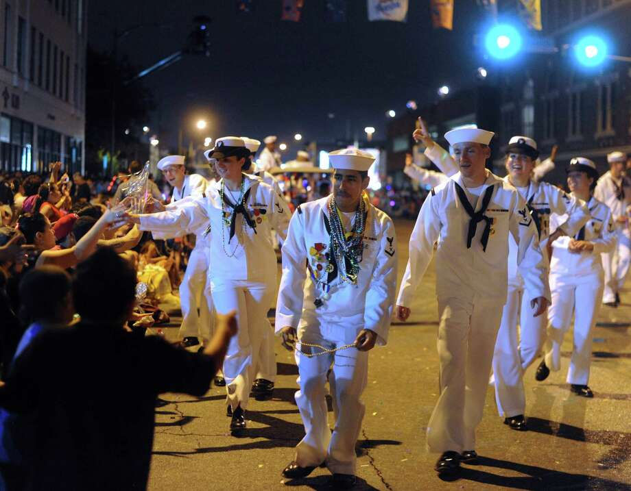 Navy personnel hand out beads during the annual Fiesta Flambeau Night Parade on Saturday, April 27, 2013. Photo: Billy Calzada, San Antonio Express-News / © 2013 San Antonio Express-News