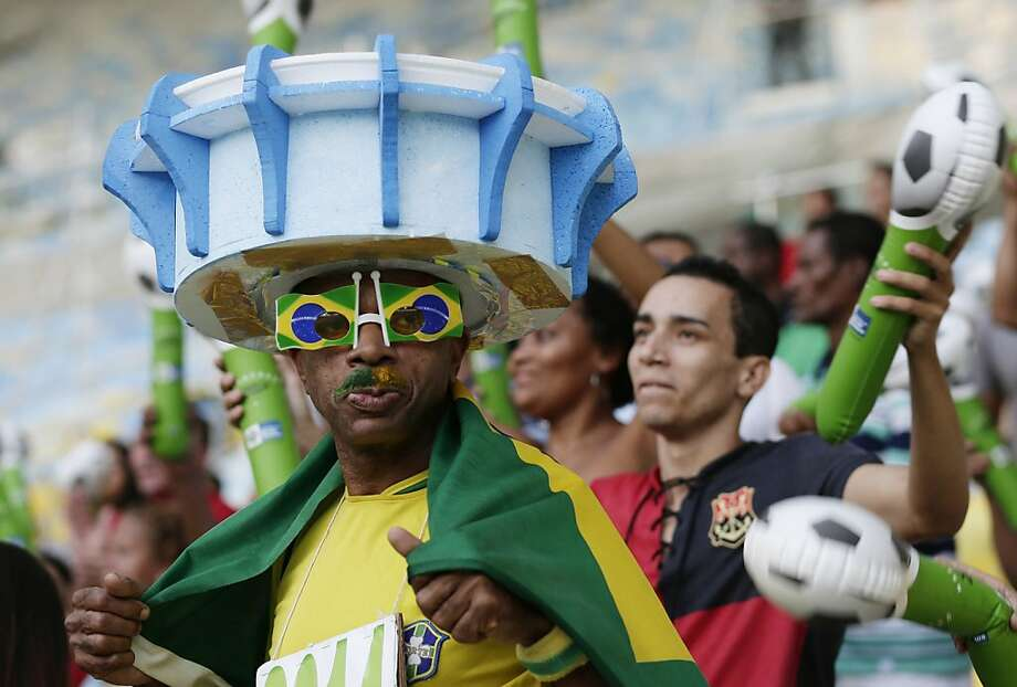 "A man wears a hat in the shape of the Maracana stadium as he arrives for the inauguration of the renovated Maracana stadium in Rio de Janeiro, Brazil, Saturday, April 27, 2013. The ""Temple of Football,"" as it's often called, is reopening as one of the most modern sporting venues in Brazil, but the improvements came amid widespread criticism related to allegations of overspending, protests against the stadium's privatization plans and construction delays. Photo: Silvia Izquierdo, Associated Press"