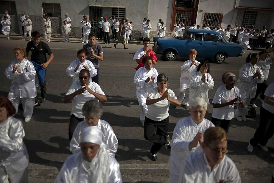 "People attend a mass Tai Chi session in the street as a classic American car drives past in the China Town area of Old Havana, Cuba, Saturday, April 27, 2013. Roberto Vargas Lee, the director of Havana's main Tai Chi school, said the session was part of global World Tai Chi Day celebrations. ""Tai Chi brings me serenity and tranquility,"" said Magaly Delgado, a 74-year-old retiree who was taking part. ""It helps me fight the stress of everyday life.""  Photo: Ramon Espinosa, Associated Press"